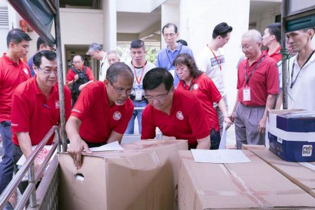 TURUN PADANG: Encik Masagos Zulkifli Masagos Mohamad (depan kiri) membantu sukarelawan dan pemimpin akar umbi memunggah kotak berisi beg cenderahati 'SG Funpack' untuk dibahagikan kepada 7,000 keluarga yang tinggal di 58 blok di Tampines. - Foto TAMPINES WEST CC
