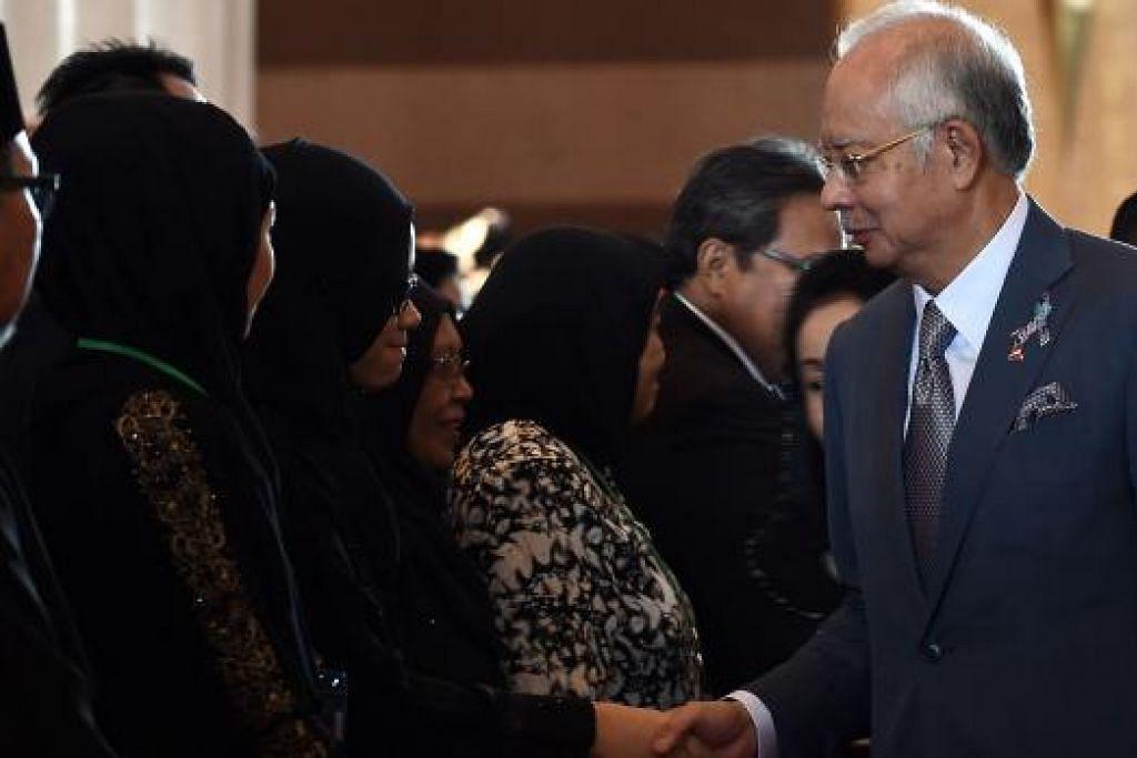 MEMPERINGATI MANGSA TRAGEDI: Datuk Seri Najib Tun Razak bersalaman dengan anggota keluarga mangsa nahas pesawat Malaysia Airlines penerbangan MH17 pada upacara memperingati tragedi tersebut di Kompleks Bunga Raya di Lapangan Terbang Antarabangsa Kuala Lumpur (KLIA) semalam. - Foto AFP