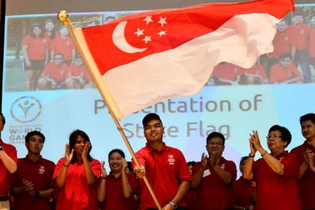SAAT MEGAH: Pemain tenis meja Nor Safik Nor Mohd Bahtiar mengibarkan bendera negara dengan megah di majlis ucap selamat semalam. – Foto SPECIAL OLYMPICS SINGAPORE