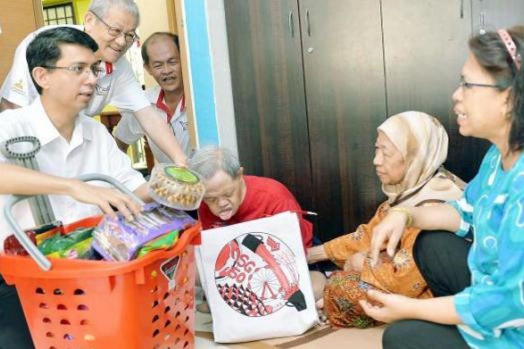 MENGHULUR SIMPATI: Dr Faishal Ibrahim bersama pemimpin akar umbi, Dr Phua Tan Tee (dua dari kiri) dan Encik Peter Kwek (tiga dari kiri), mengunjungi pesakit Sindrom Down, Encik Abdul Halim, ibunya, Cik Suraia Hitam dan kakak iparnya, Cik Awiyah Kasim. - Foto KHALID BABA