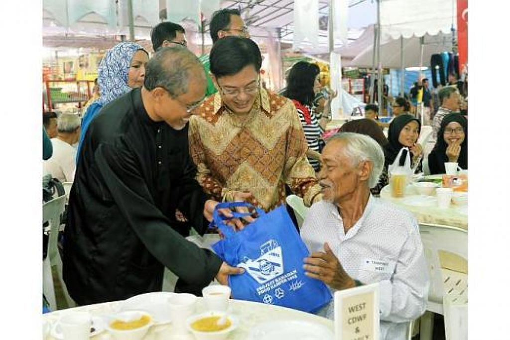 HABUAN UNTUK PENDUDUK: Encik Masagos (kiri) dan Encik Heng (tengah) memberi habuan makanan kepada seorang penduduk di majlis pelancaran pengagihan hamper makanan Ramadan Tampines. - Foto KHALID BABA