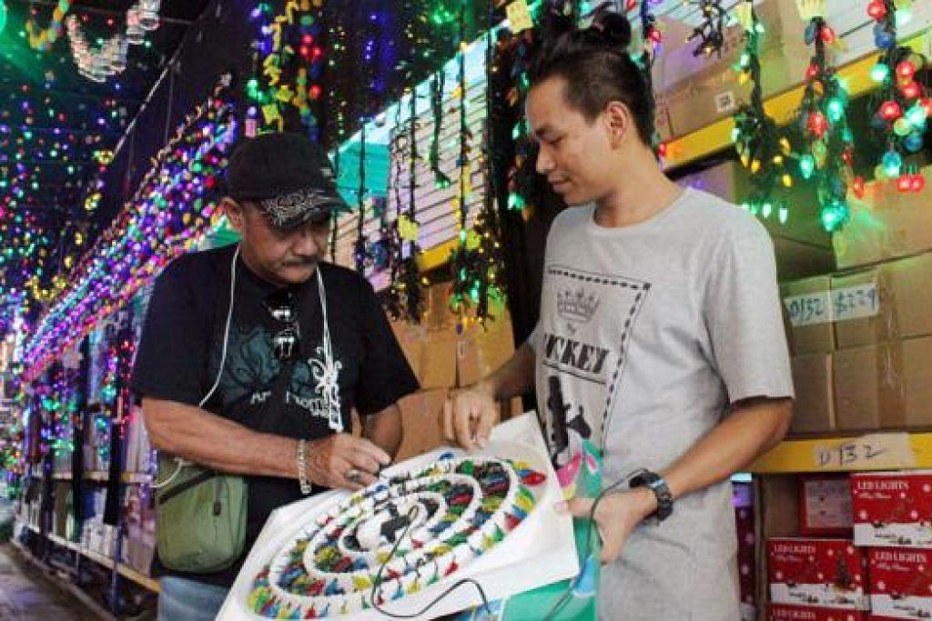 TERTARIK PADA PANDANGAN PERTAMA: Pelanggan baru gerai First Price, Encik Abdul Hamid Ayob (kiri), sedang memeriksa perhiasan lampu lap-lip yang ingin dibelinya bersama seorang pekerja, Encik Min Tun. - Foto SITI AISYAH NORDIN
