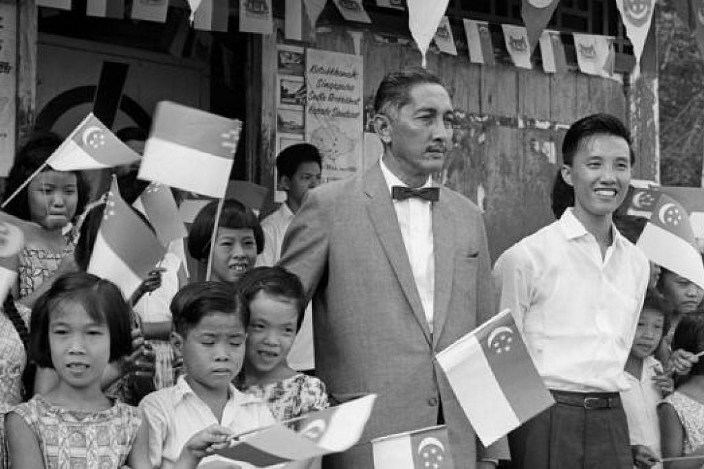 BERSAMA RAKYAT: The Yang di-Pertuan Negara, Encik Yusof Ishak, bersama Encik Ong Chang Sam, Ahli dewan Chua Chu Kang, bergambar bersama sekumpulan kanak-kanak yang mengibarkan bendera di Kampong Keat Hong ketika melawat kawasan Chua Chu Kang.  - Foto THE STRAITS TIMES