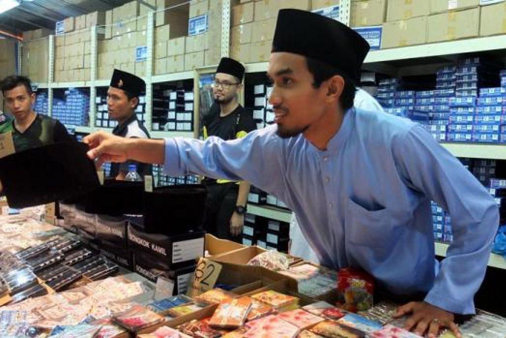 SONGKOK UNTUK MELENGKAPI BAJU MELAYU: Kakitangan di sebuah gerai menjual songkok sibuk tetapi ghairah melayani pelanggan yang ingin membeli songkok.