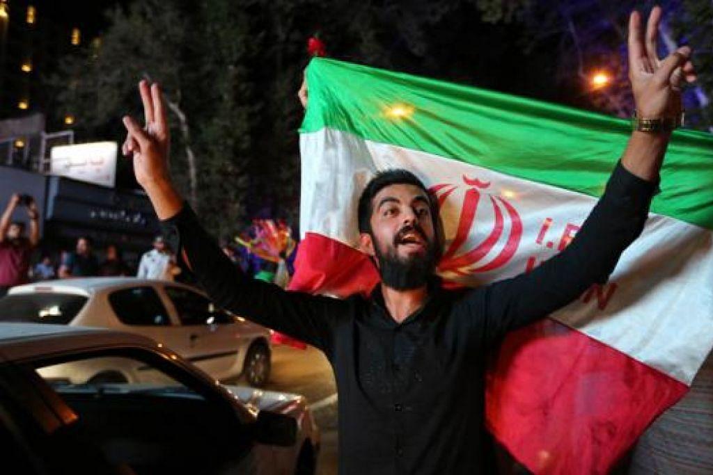 RAIKAN PERJANJIAN: Seorang lelaki Iran menunjukkan tanda kemengangan di utara Teheran kelmarin selepas Iran berjaya memeterai perjanjian nuklear dengan negara kuasa dunia. - Foto AFP