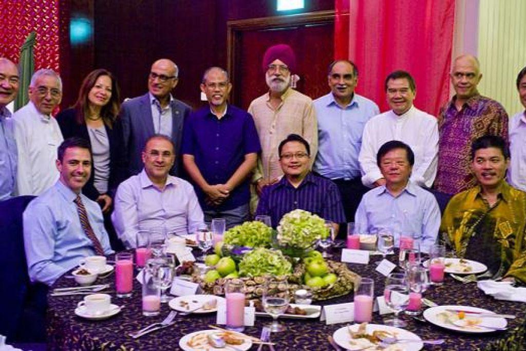 ERATKAN HUBUNGAN: Para tetamu majlis iftar yang dihos Encik Raffin (empat dari kiri, berdiri) - termasuk Encik Masagos (tengah), Encik Andri Hadi (dua dari kanan, berdiri) dan Encik Abdullah (sebelah kanan Encik Andri) - berpeluang menjamu hidangan istimewa bersama dan beramah mesra. - Foto TUNI SHARIFF
