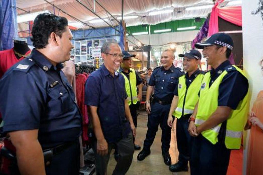 PENGHARGAAN BUAT PEGAWAI BERTUGAS: Encik Masagos (dua dari kiri) bercakap dengan beberapa pegawai polis yang bertugas semasa kunjungannya ke bazar Geylang Serai kelmarin. - Foto M.O. SALLEH