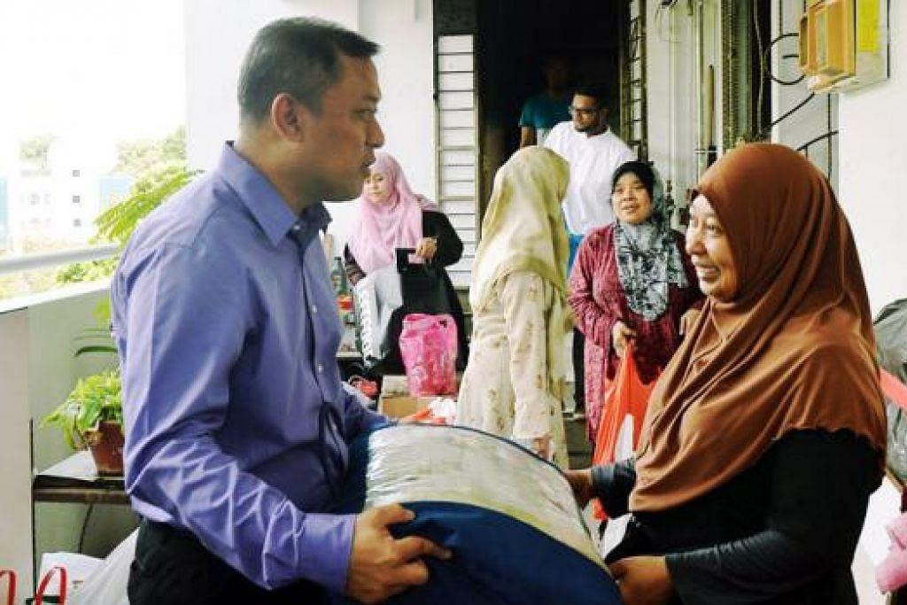 HULUR BANTUAN: Haji Rahim bersama kakitangan Masjid An-Nur menziarahi rumah Cik Azlena di Marsiling Drive semalam untuk memberikan bantuan termasuk wang derma yang dikutip kakitangan masjid serta orang ramai. - Foto KHALID BABA