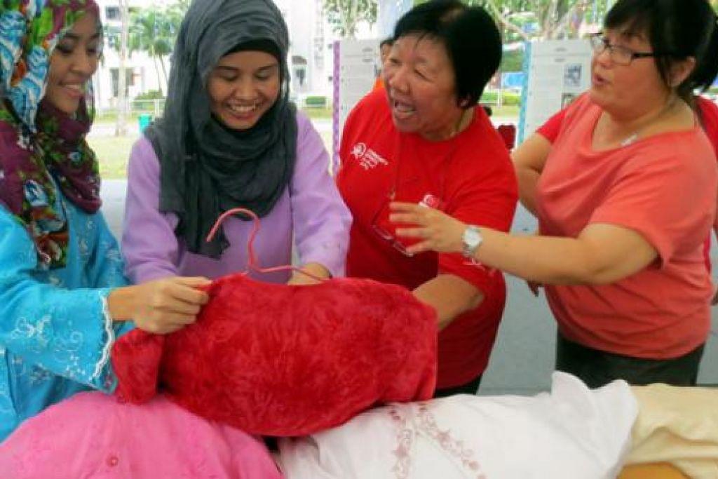 PUPUK SIFAT YAKIN DIRI: (Dari kiri) Cik Nadra dan ibunya, Cik Norashikin, bermesra bersama pengunjung bukan Melayu/Islam yang ingin mencuba baju kurung untuk bergambar. - Foto HARI RAYA LIGHT UP COMMITTEE