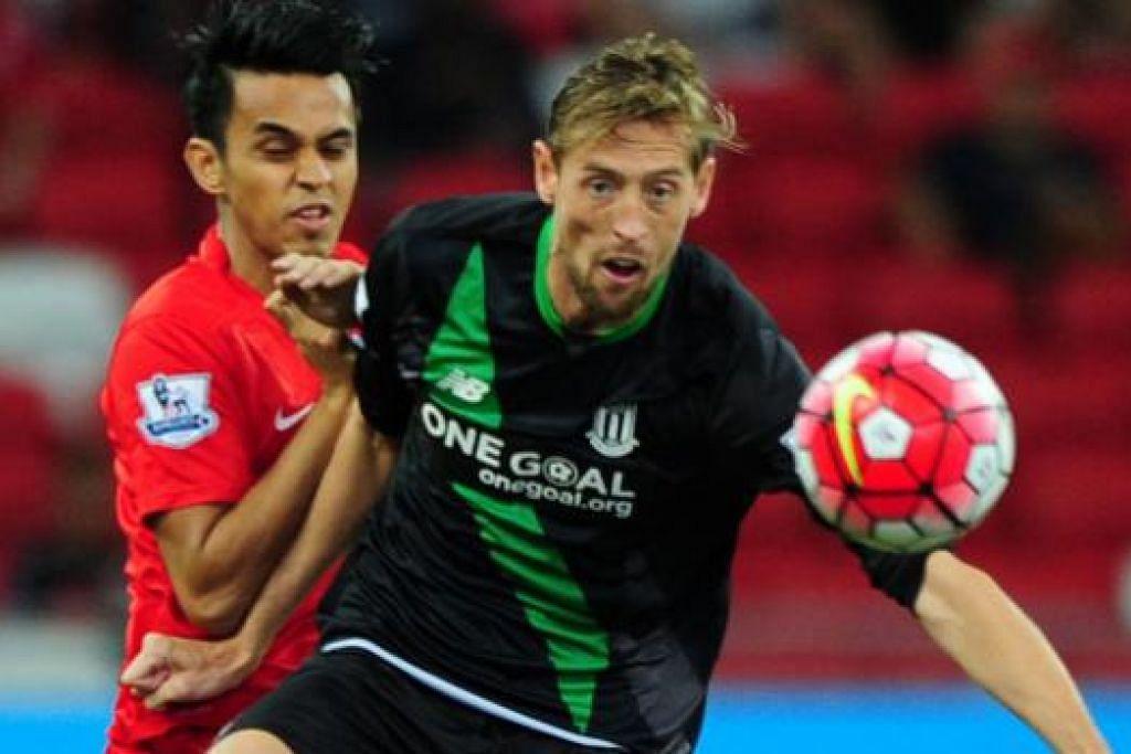 KAWAL BOLA: Penyerang Stoke City, Peter Crouch (depan), mengawal bola daripada cuba diadang oleh pemain pasukan Pilihan Singapura, Shahdan Sulaiman.