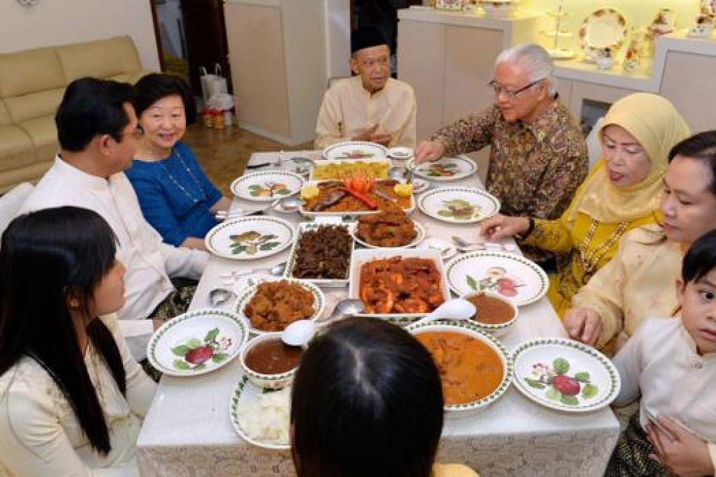 TEMAN LAMA: Presiden Tony Tan (empat dari kanan) dan isterinya Cik Tan (baju biru) menjamu selera di rumah Haji Othman (tengah) bersama keluarganya. - Foto M.O. SALLEH