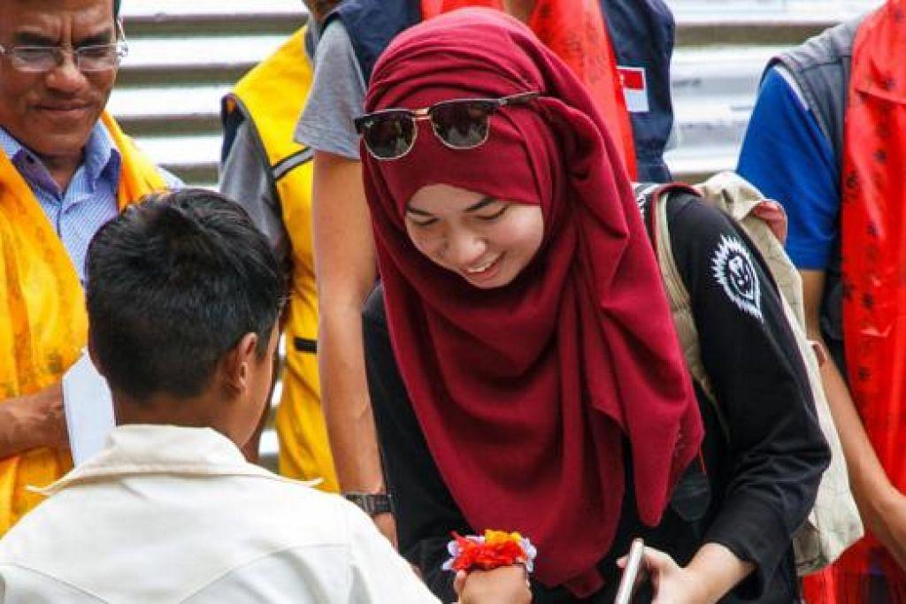 SAMPAIKAN PENGHARGAAN: Pelajar Sekolah Menengah Bageswori memberi jambangan bunga kecil kepada wartawan Siti Aisyah setelah menerima beg dan keperluan sekolah lain. - Foto ALEXANDRA TOH MEI-YING