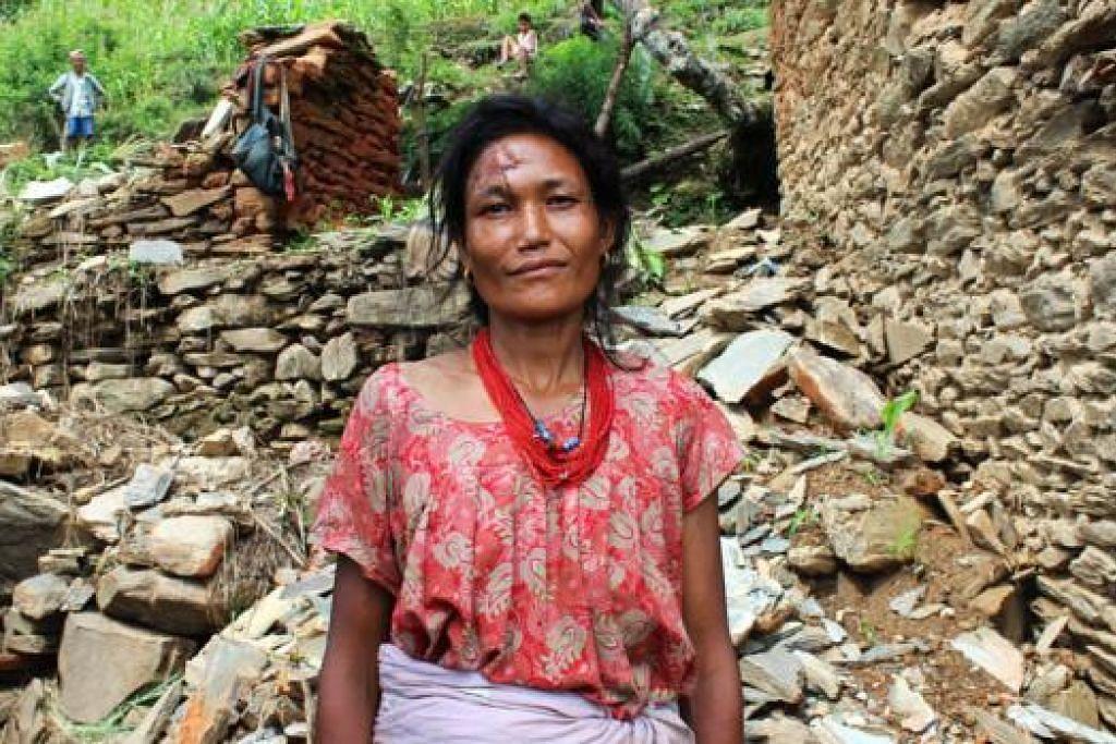 POSITIF WALAU KESUSAHAN: Cik Shanta Maya Strestha berdiri di tapak rumahnya yang musnah. Beliau sendiri cedera di kepala. Namun, Cik Shanta masih positif akan pemulihan kampungnya. - Foto SITI AISYAH NORDIN