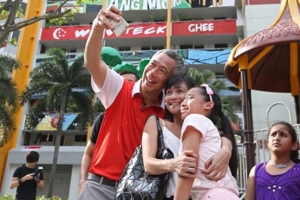 'SENI' BINA: Encik Lee memetik 'selfie' bersama penduduk di pelancaran Pesta PassionArts di Teck Ghee semalam. Beliau memberi sentuhan terakhir lukisan pada kanvas yang kemudian digunakan untuk melengkapkan lukisan pada blok di belakangnya. - Foto THE STRAITS TIMES