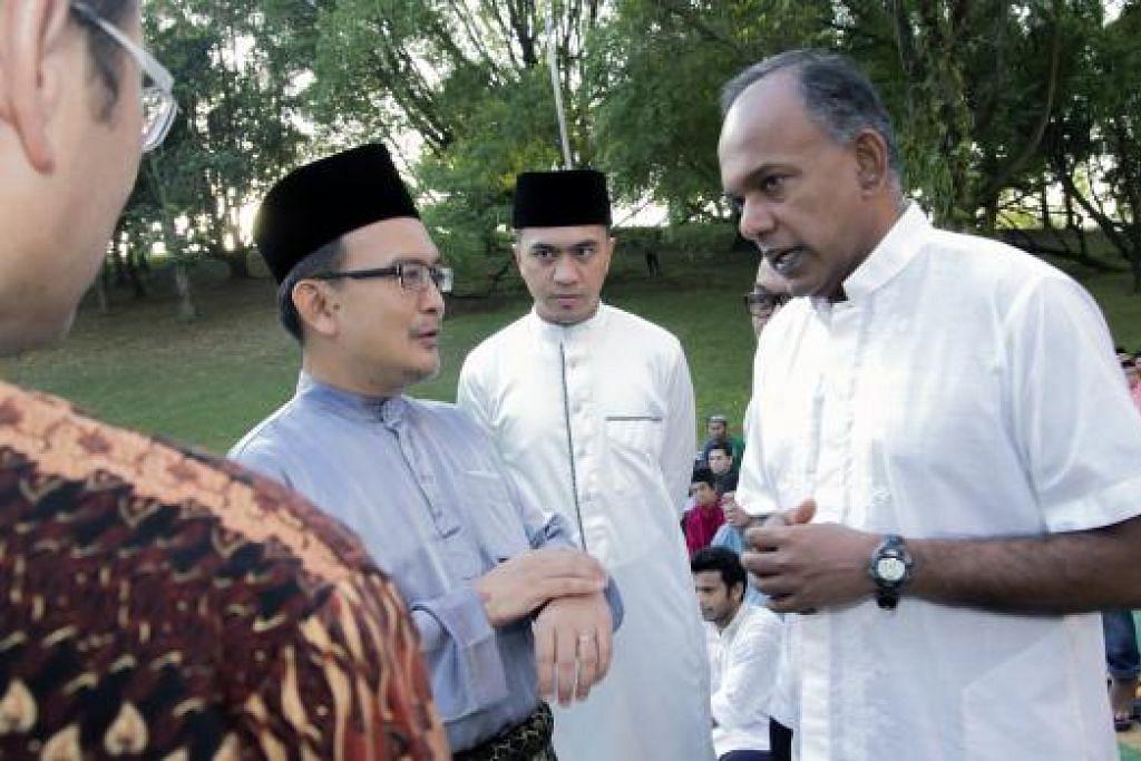SAMBUT SYAWAL: Pengerusi Eksekutif Masjid Darul Makmur, Encik Khalid Shukur Bakri (dua dari kiri) bersama dengan Encik Shanmugam di Masjid Darul Makmur kelmarin. - Foto MUHD FAUZEE ABDUL RAHIM