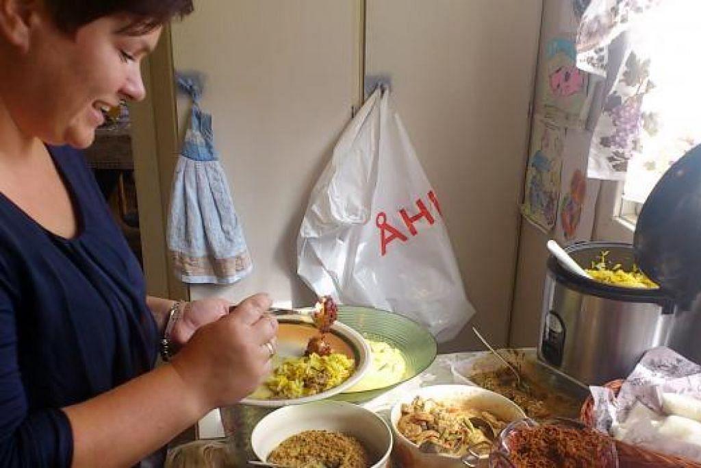 RUMAH TERBUKA: Salah seorang tetamu yang menghadiri rumah terbuka Cik Suriati Supani di rumahnya di Norway sedang menjamu selera juadah Hari Raya seperti lauk lodeh, sambal goreng dan sambal tumis yang dimasak Cik Suriati (atas). - Foto ihsan SURIATI SUPANI