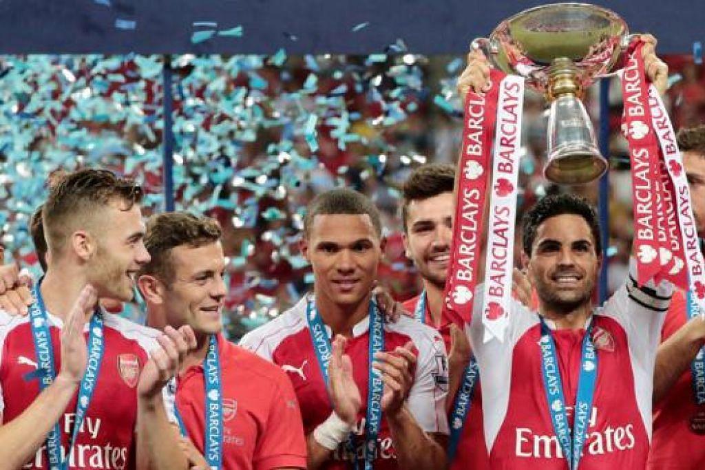 RAIKAN KEJUARAAN: Bintang midfield Arsenal, Mikel Arteta, menjulang mahkota Asia Barclays, menyusuli kemenangan 3-1 ke atas Everton kelmarin. - Foto REUTERS