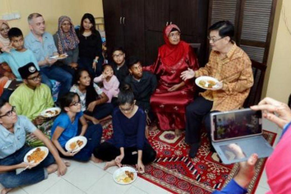 RAYA BERSAMA: Encik Heng (kanan) berbual mesra dengan Hajah Mahamooda (dua dari kanan) dan keluarga beliau semasa lawatan sempena Hari Raya di flat satu bilik Hajah Mahamooda di Tampines Street 83 semalam. - Foto TAUFIK A. KADER