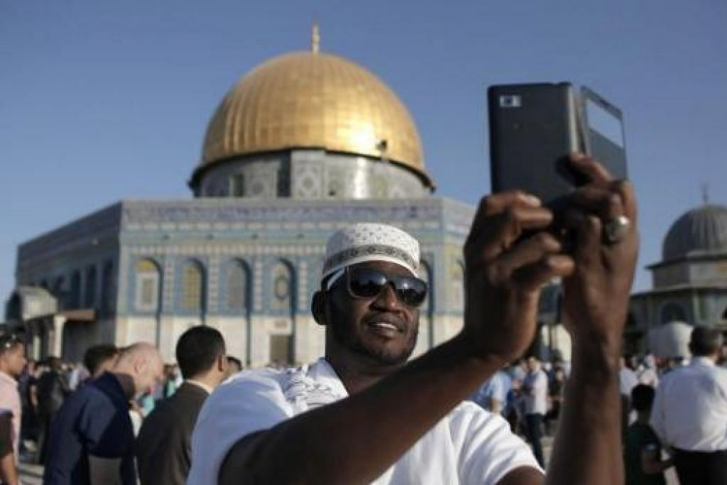 BUAT KENANGAN: Seorang jemaah dari Afrika memetik 'selfie' di hadapan Qubbat As-Sakhrah atau Kubah Batu yang terletak bersebelahan Masjid Al-Aqsa di Baitulmakdis. - Foto AFP