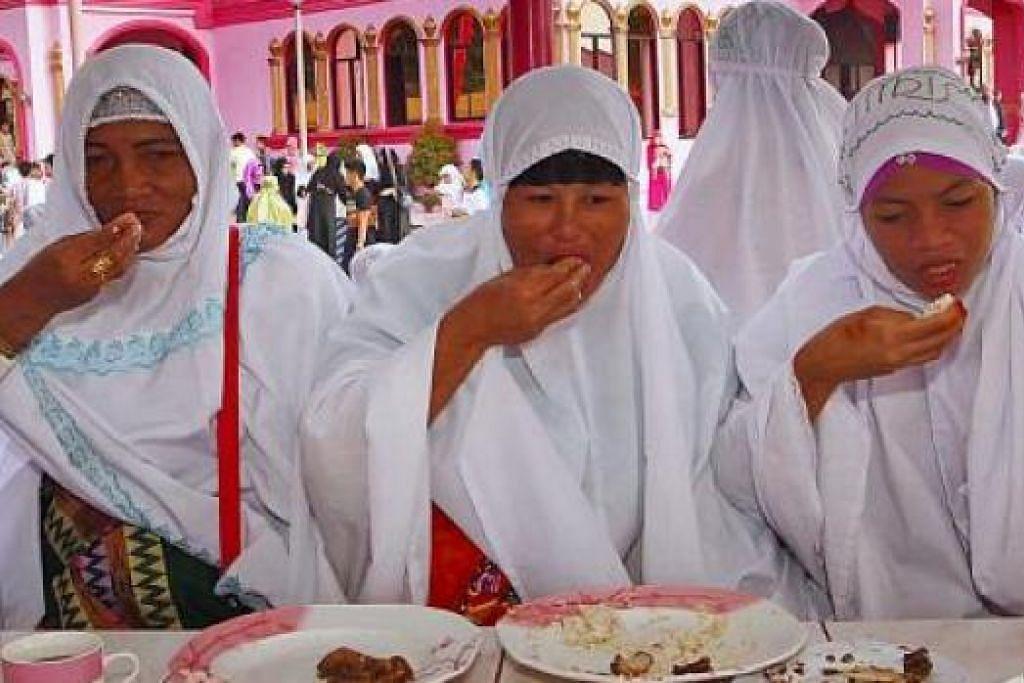 DAH TAK PUASA: Jemaah wanita menikmati juadah Hari Raya selepas menunaikan solat Aidilfitri di perkarangan Masjid Merah Jambu di kota Datu Saudi Ampatuan di Maguindanao, Filipina. - Foto REUTERS