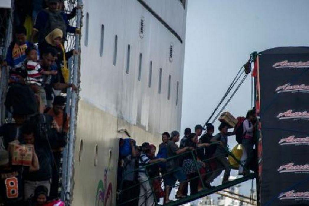 TAK ADA KERETA API, KAPAL PUN JADI: Sebuah kapal yang sarat membawa penumpang Islam yang ingin pulang ke desa 'memuntahkan' isinya sejurus tiba di dermaga pelabuhan Surabaya di Timur Jawa. - Foto AFP