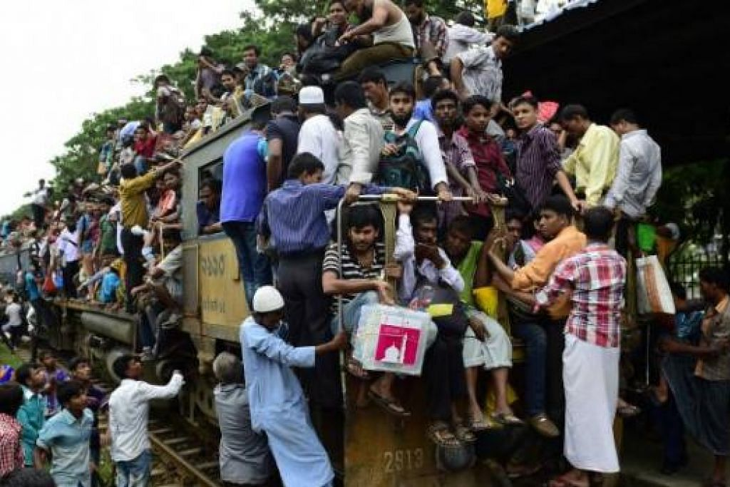 ADA RUANG LAGI KE?: Warga Bangladesh bergayut daripada setiap ruang yang ada pada kereta api dalam usaha mereka pulang ke kampung masing-masing untuk menyambut Aidilfitri. - Foto AFP