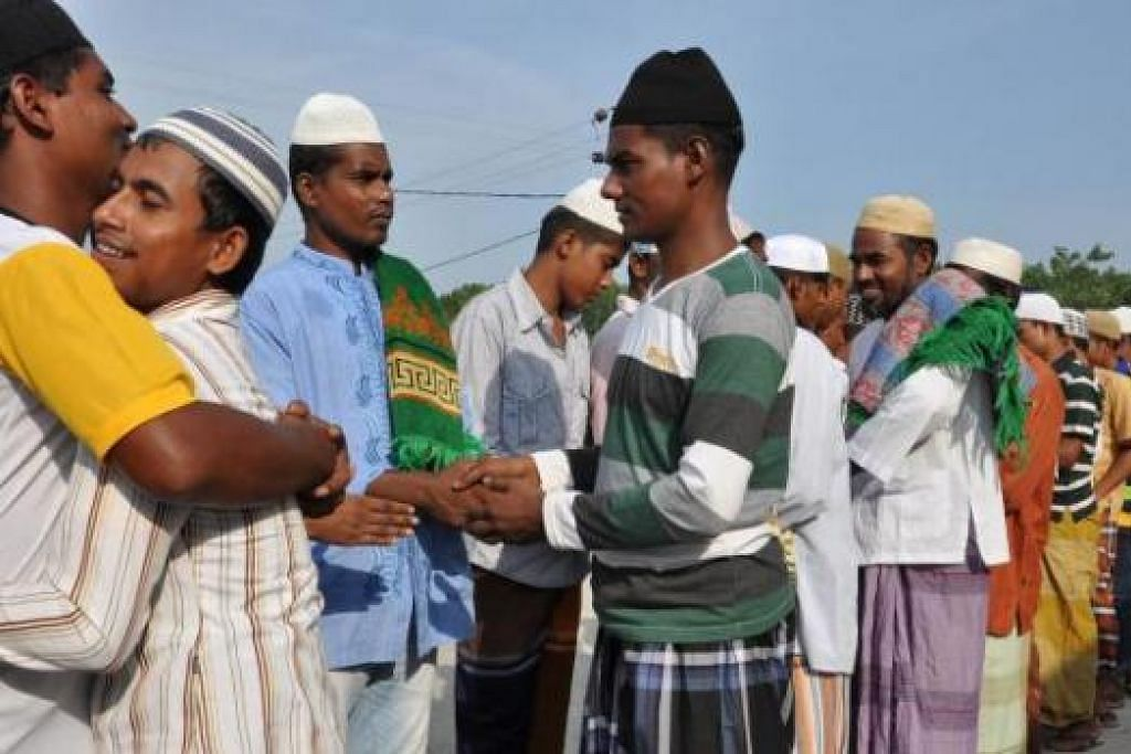 BERAYA DI KHEMAH PELARIAN: Pendatang Rohingya and Bangladesh bermaaf-maafan di antara satu sama lain selepas menunaikan solat Aidilfitri di kem pelarian di Langsa, Aceh. - Foto AFP