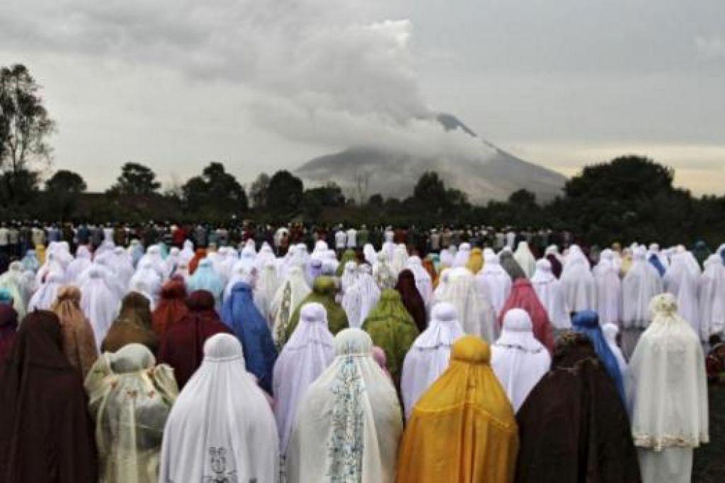 MENGAGUNGKAN TUHAN PENCIPTA ALAM SEMESTA: Penduduk kampung Ndokum Siroga di Karo, Sumatera Utara, yang tinggal di kaki gunung berapi Sinabung, menunaikan solat Aidilfitri berlatarbelakangkan kepulan asap yang terbit daripada gunung tersebut, kelmarin. - Foto REUTERS