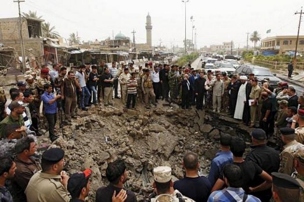 KAWAH AKIBAT LETUPAN BOM KERETA: Penduduk dan pasukan keselamatan Iraq berhimpun di kawah berukuran kira-kira lima meter lebar dan dua meter dalam akibat letupan bom kereta di pasar di Khan Bani Saad, Baghdad, semasa sambutan Hari Raya Aidilfitri. - Foto Reuters.