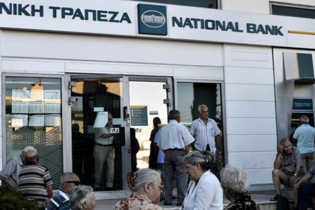 TUNGGU DI LUAR BANK: Ramai warga tua menunggu di luar sebuah bank di Athens, Greece, bagi mengeluarkan wang mereka. Pemerintah telah memerintahkan penutupan bank yang berjalan hampir tiga minggu dan ia mula dibuka semalam. - Foto AFP