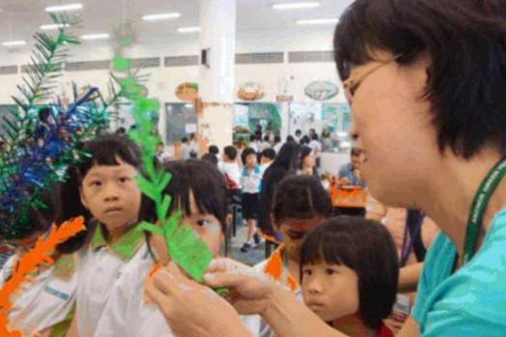TIMBA KEMAHIRAN BARU: Pelajar Sekolah Rendah Anchor Green diajar cara membuat bunga manggar semasa sambutan Hari Keharmonian Kaum yang diraikan semalam.