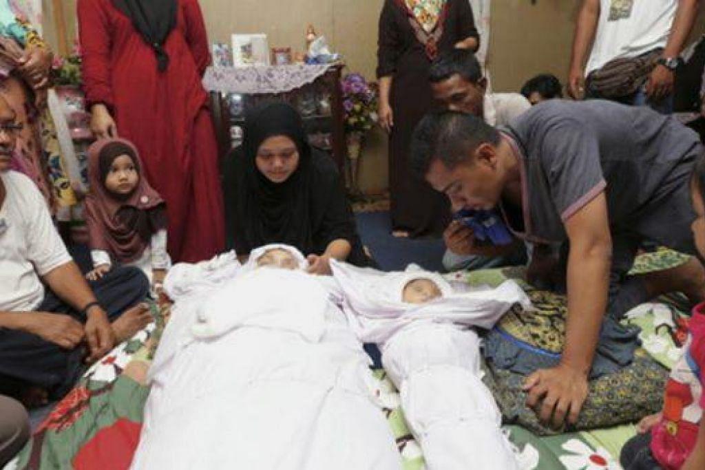 MANGSA NAHAS: Encik Shahrul Raziman tunduk untuk mengucup jenazah anak dan isterinya yang terkorban dalam kemalangan jalan raya. - Foto THE STAR