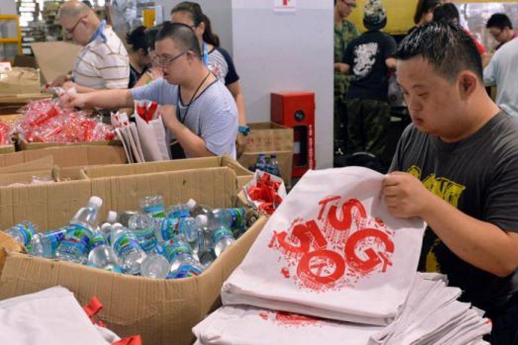 TURUT MEMBANTU: Pertubuhan Kebajikan Sukarela (VWO) seperti Persatuan Sindrom Down (DSA) turut membantu menyiapkan 'SG Funpack' di Kranji Camp 3 semalam. - Foto KHALID BABA