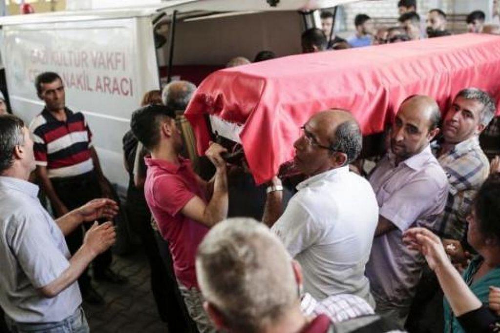 MULA DIKEBUMIKAN: Orang ramai membawa keranda mangsa serangan bom nekad militan IS di Suruc dengan sekurang-kurangnya 30 orang terkorban dalam serangan ganas itu. - Foto AFP