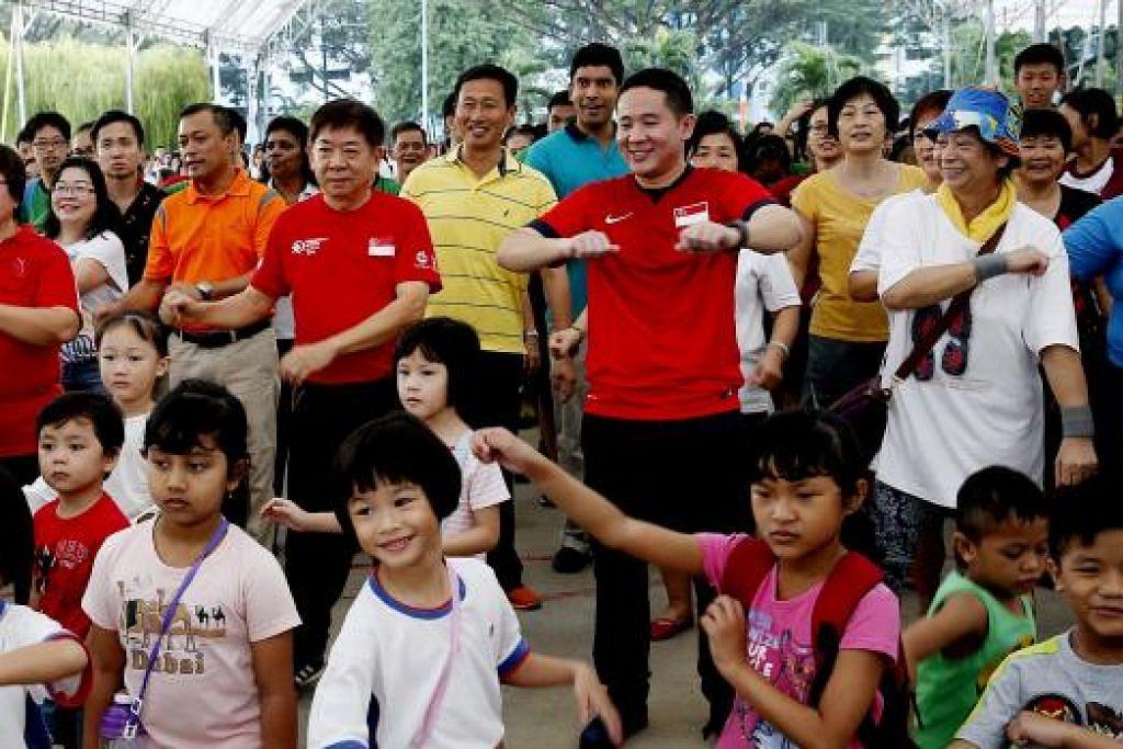 SENAMAN BERSAMA: (Dari kiri berbaju merah) Cik Ellen Lee, Encik Khaw Boon Wan dan Encik Amrin Amin sama-sama bersenam dengan penduduk dan tetamu yang hadir bagi acara berjalan bersama. - Foto ST