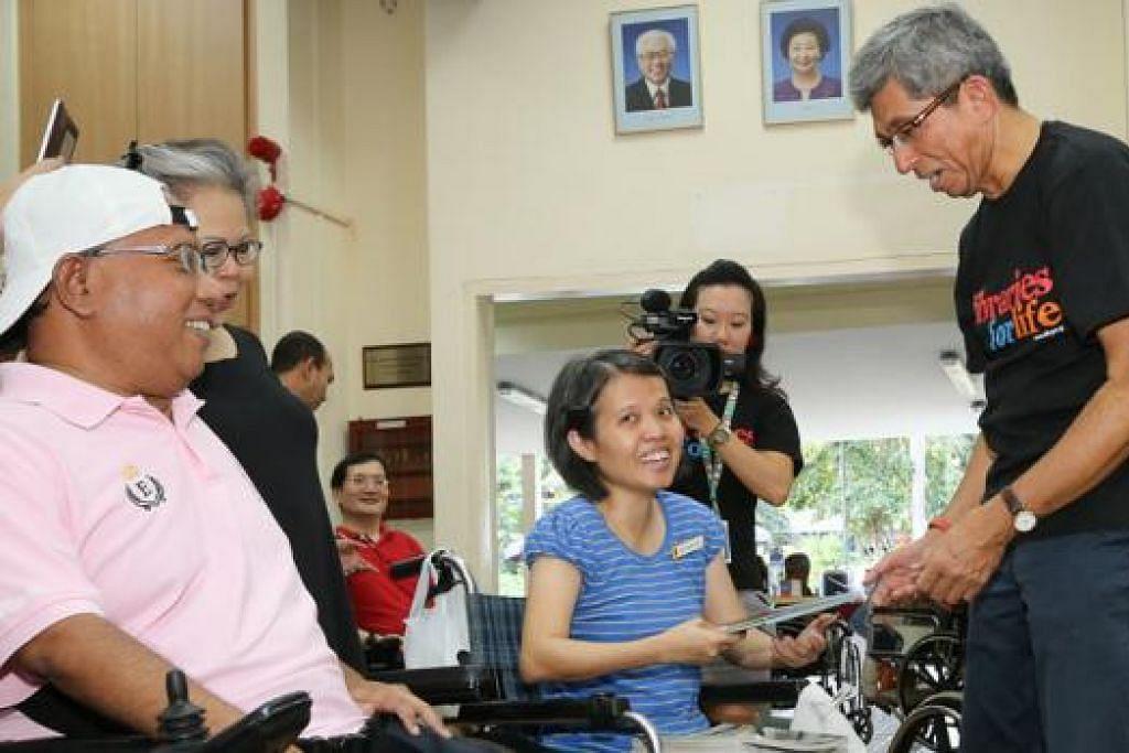 UNTUK SEMUA: Dr Yaacob Ibrahim (berdiri) bersama sukarelawan inisiatif 'Project Deliver Me' berinteraksi dan memberi beberapa buku kepada penghuni Singapore Cheshire Home semasa kunjungan mereka semalam. - Foto NLB