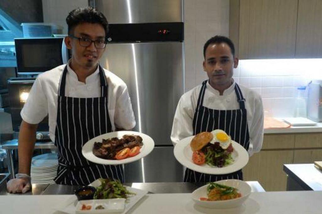 MASAK DI DEPAN MATA: Pelanggan boleh melihat cef Encik Fakhruli Islam Mohd Shah (kiri) dan Encik Mohd Imran menyediakan sajian stik di restoran berkonsep terbuka di The Royals Steakhouse di Jalan Pisang.