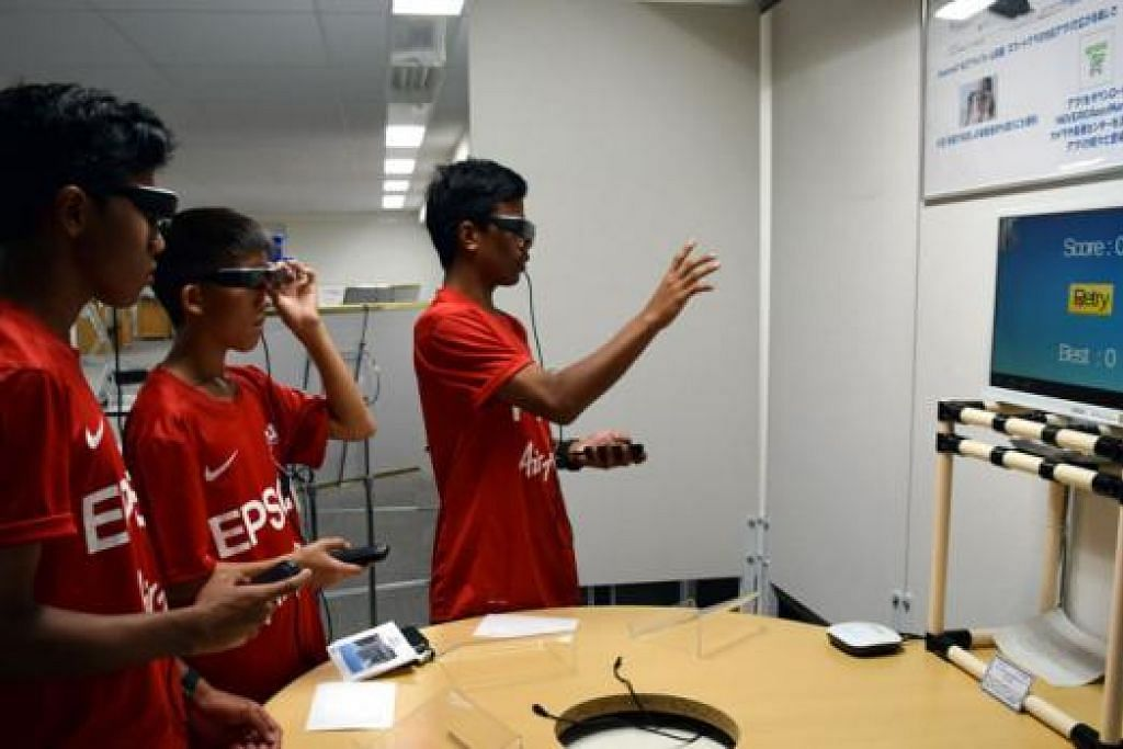 KACA MATA CANGGIH: Pemain U-14 Singapura (dari kiri) Hamizan, Elijah dan Adam gembira dapat mencuba kaca mata canggih buatan Epson. - Foto HAKIM YUSOF