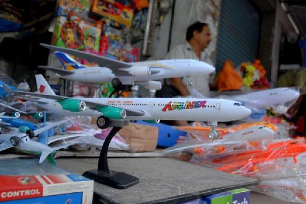 TANDA PENGHARGAAN: Mainan kapal terbang ini amat popular di kalangan pelawat yang datang dengan hajat agar permohonan visa mereka ke luar negara diluluskan. Ia diberi kepada sebuah kuil apabila permohonan visa mereka diluluskan. - Foto AFP