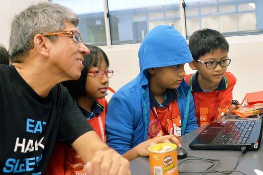 HACKATHON: Dr Yaacob Ibrahim melihat pelajar (dari kiri) Lau Tat Hong, Aras Aman Ajit dan Hin Sat Phyu dari Sekolah Rendah Balestier Hill menjelaskan projek mereka dalam acara Hackathon @SG2015 semalam. - Foto KHALID BAB