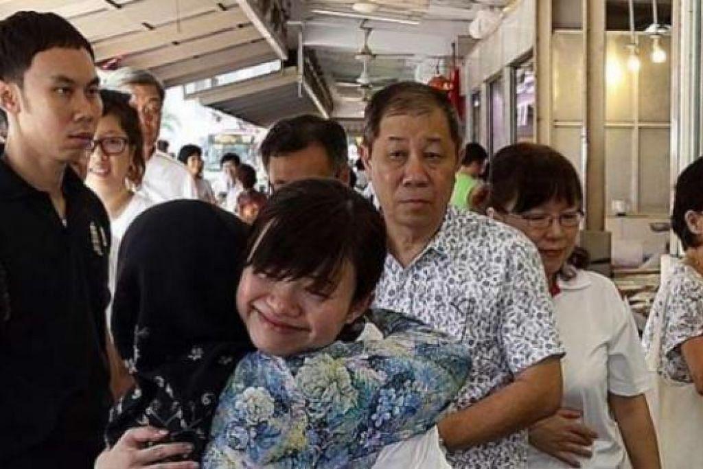 MESRA: Cik Tin Pei Ling (berbaju putih) dipeluk oleh seorang penduduk MacPherson, Cik Fatimah Buang, 75 tahun, semasa Cik Tin melawat sebuah pasar di kawasan undi itu kelmarin. - Foto THE STRAITS TIMES