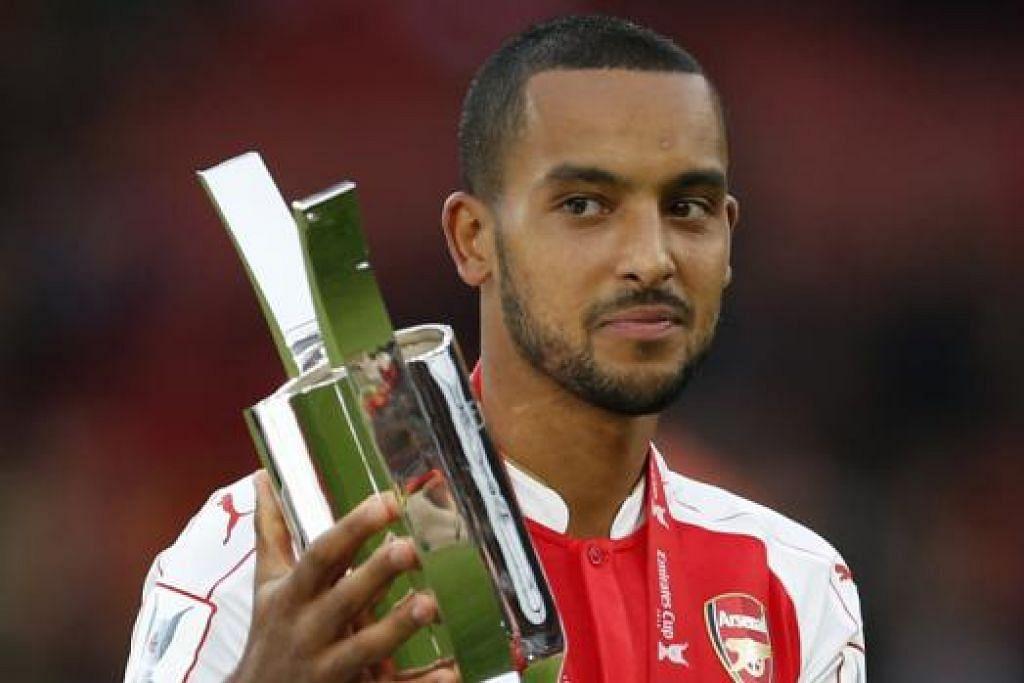 WIRA PASUKAN: Penjaring gol kemenangan Arsenal, Theo Walcott, bergambar dengan trofi kejuaraan Piala Emirates. - Foto REUTERS