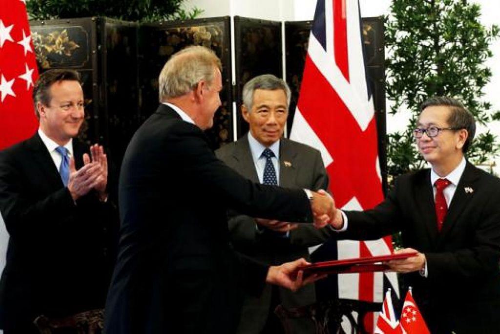 DEMI KESELAMATAN SIBER: Encik Cameron (kiri) dan Encik Lee (dua dari kanan) menyaksikan pemeteraian Memorandum Persefahaman (MOU) mengenai Kerjasama Keselamatan Siber yang ditandatangani oleh Encik Koh (kanan) dan Sir Nigel di Istana semalam. - Foto THE STRAITS TIMES