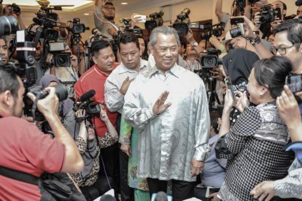 BERSIAP BERI PENJELASAN: Mantan Timbalan Perdana Menteri Malaysia Tan Sri Muhyiddin Yassin, yang dipecat kelmarin, melambai-lambai ke arah wartawan setibanya beliau bagi mengadakan sidang akhbar semalam. - Foto AFP