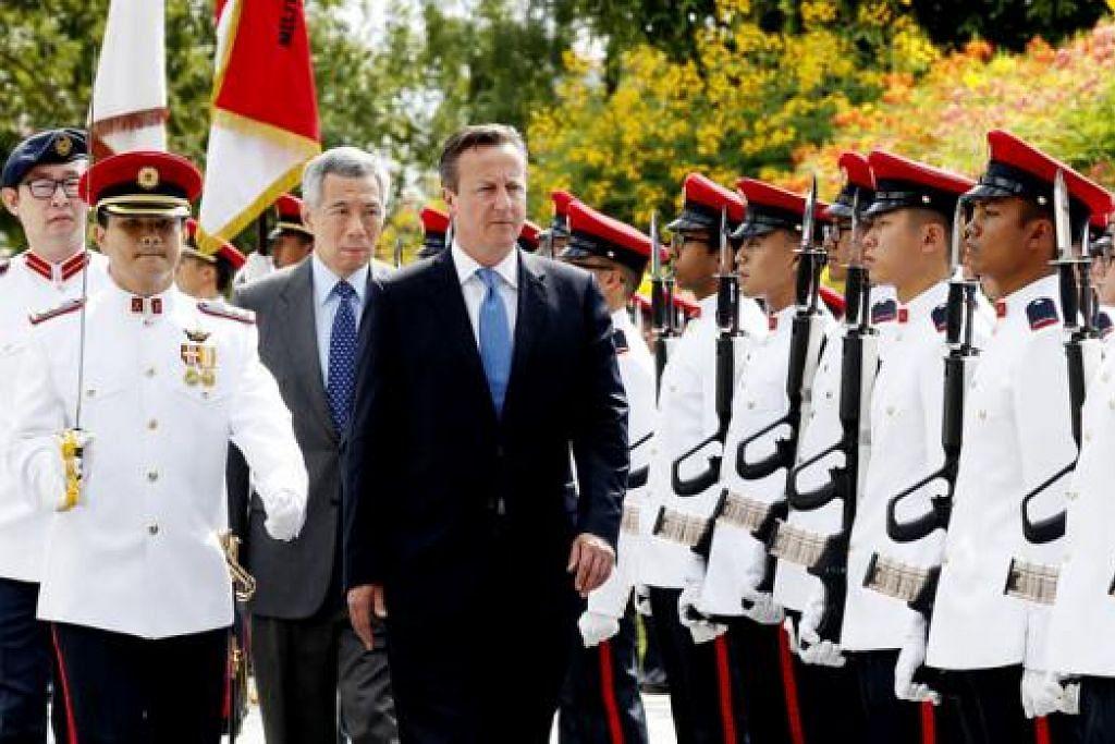 UPACARA PENUH HORMAT: Perdana Menteri Britain, Encik David Cameron (bersut biru), disambut dalam satu upacara beristiadat di Istana semalam. Bersamanya ialah Perdana Menteri Lee Hsien Loong (bersut kelabu). - Foto THE STRAITS TIMES