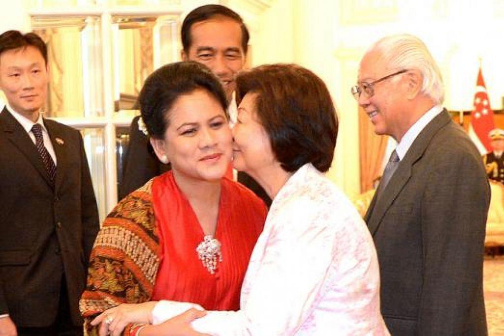 DAKAPAN MESRA: Isteri Presiden Joko Widodo, Cik Iriana, dan Isteri Presiden Tony Tan, Cik Mary Tan, berdakapan di Istana.