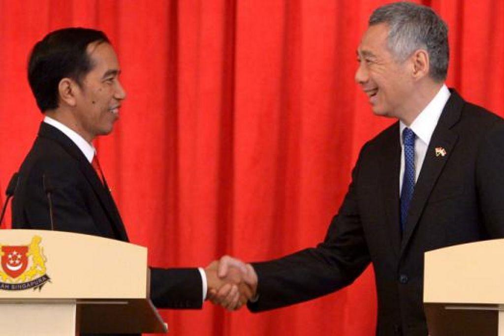 PERKUKUH JALINAN: Presiden Joko Widodo berjabat tangan dengan Perdana Menteri Lee Hsien Loong selepas sidang media di Istana, kelmarin.