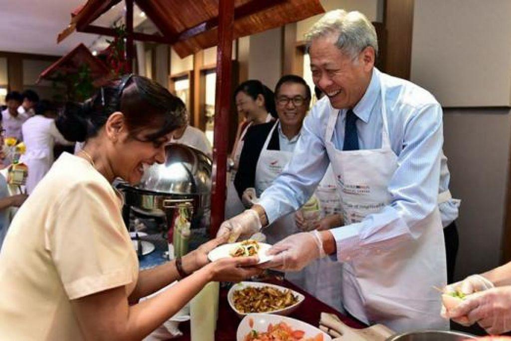 SAMBUT HARI JURURAWAT: Dr Ng menghidangkan makanan kepada jururawat semasa sambutan Hari Jururawat di SGH semalam. - Foto NG ENG HEN FACEBOOK