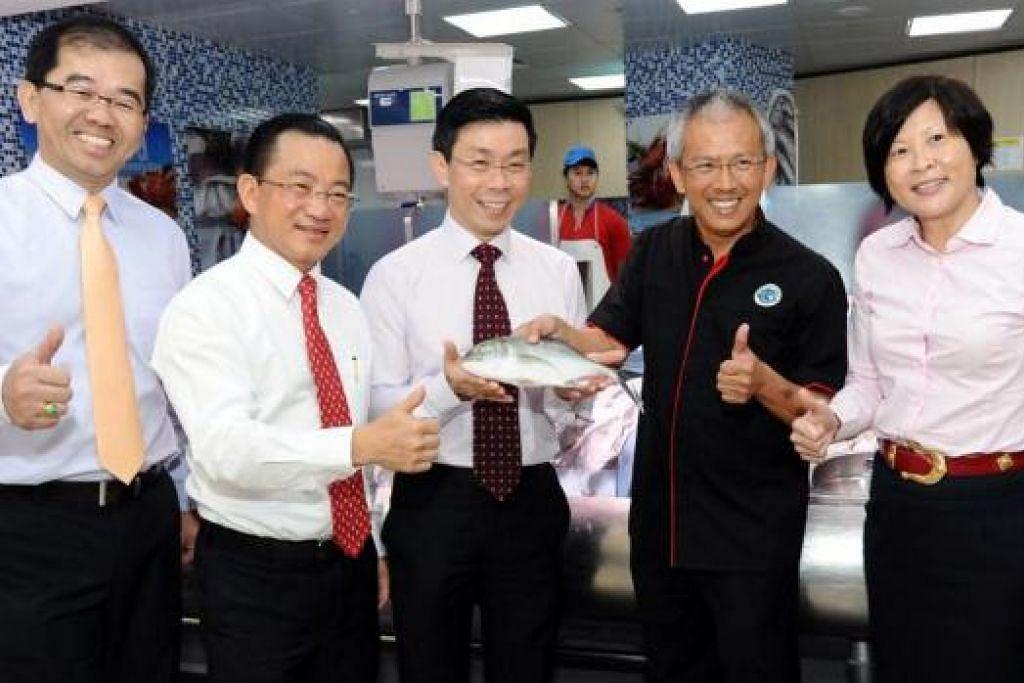 PROMOSI PRODUK SINGAPURA: Menteri Negara Kanan (Perdagangan dan Perusahaan), Encik Lee Yi Shyan (tiga dari kiri), memegang ikan yang diternak di Singapura dan dijual di NTUC FairPrice. Bersamanya ialah CEO NTUC FairPrice, Encik Seah Kian Peng (dua dari kiri), serta wakil NTUC FairPrice dan SME. - Foto NTUC