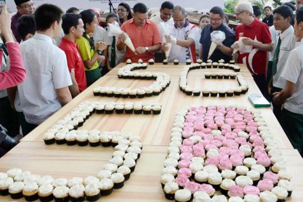 KEK CAWAN SG50: Encik Masagos Zulfkifli (tengah) dan pengurus Kelab Masyarakat Tampines West, Encik Suhaimi Rafdi (berbaju kuning air); naib pengetua Sekolah Menengah Springfield (berbaju hitam); dan pengurus Masjid Darul Ghufran, Encik Abdul Matin (berbaju merah) serta sukarelawan menghasilkan logo SG50 dengan 500 kek cawan. - Foto TAUFIK A KADER